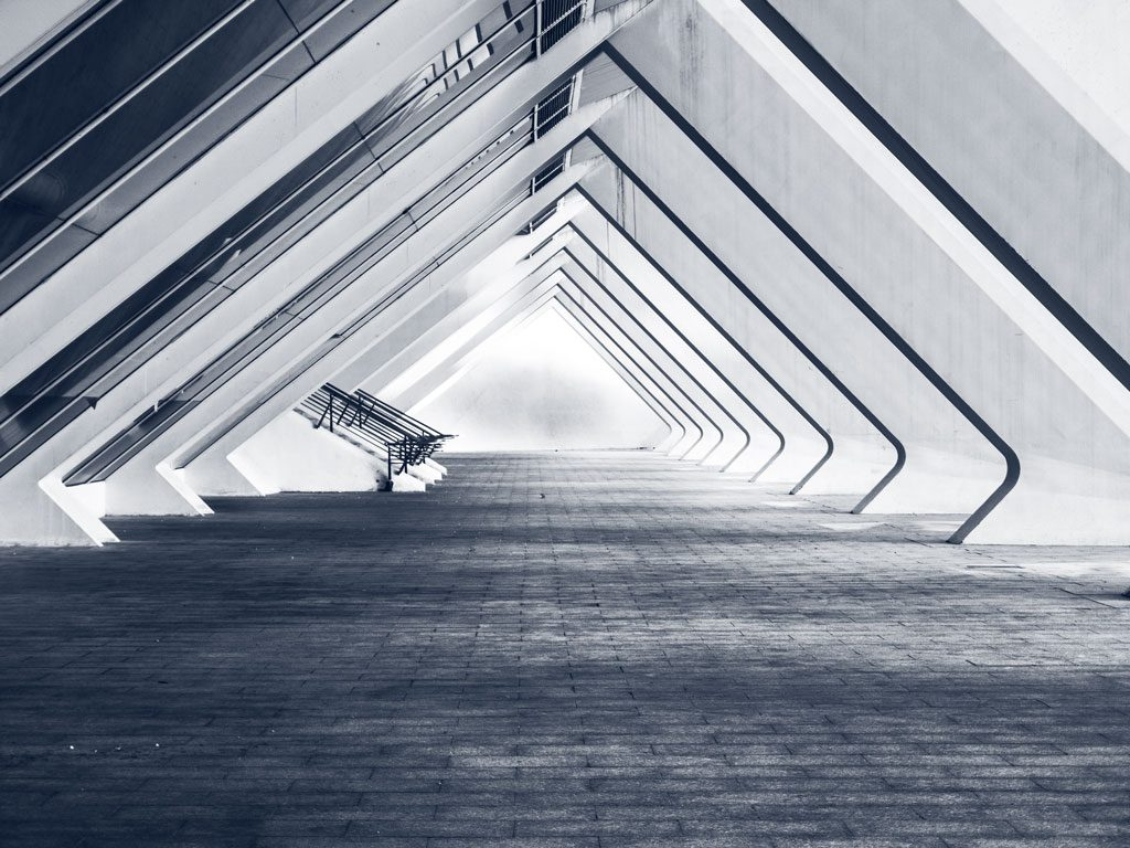 A triangular archway created with slatted diagonal concrete, glass and steel - creating a dramatic structural effect