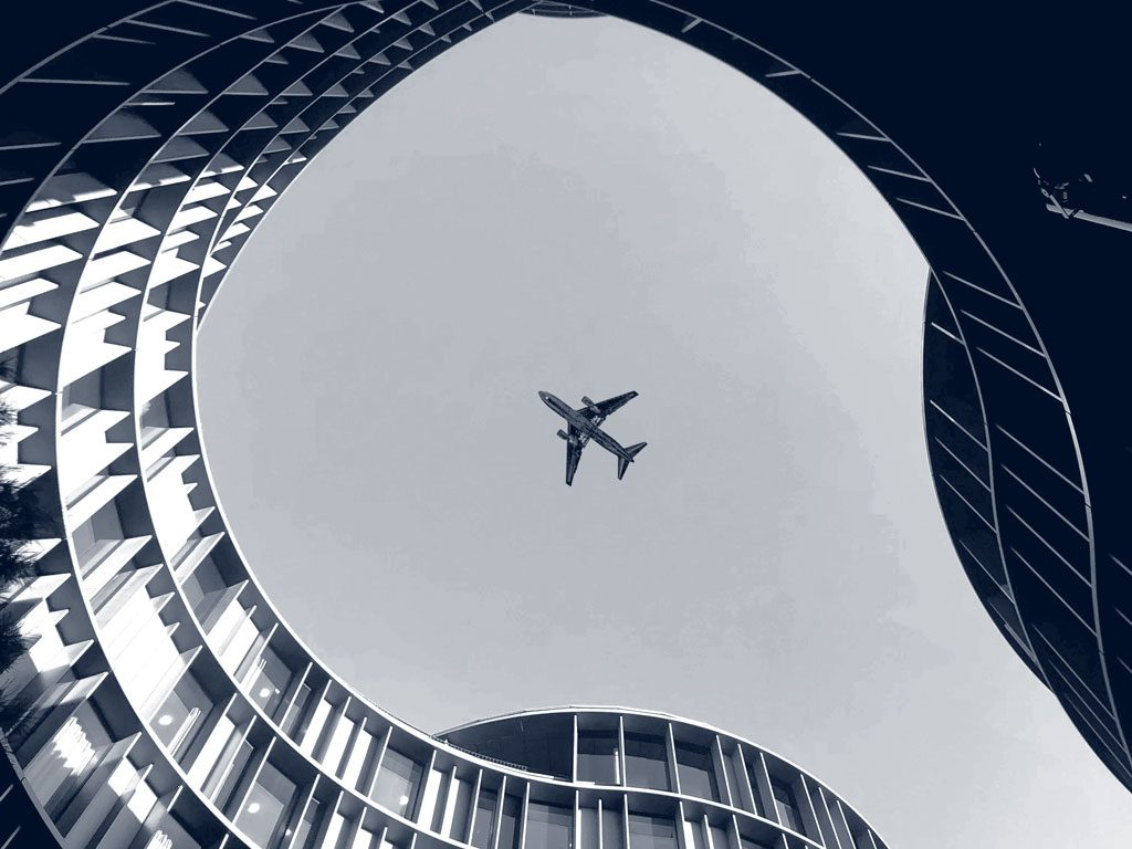 An aeroplane is captured flying over a curved building looking up.