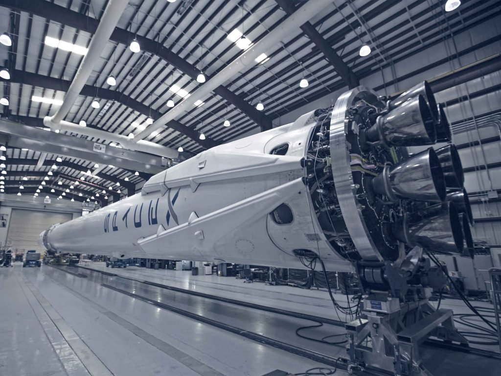 A spacex rocket in a warehouse with shining lights above illuminating the entire factory