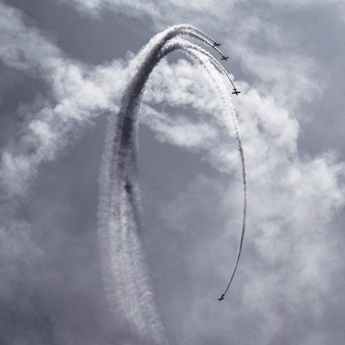 Four aeroplanes perform aerial acrobatics with smoke in the clouds - they are mid loop.